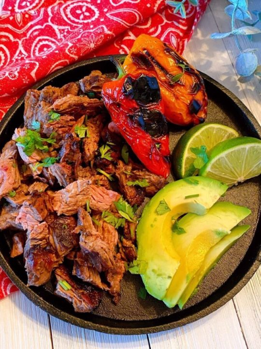 Carne Asada on a black skillet with sliced avocado, roasted peppers, and lime wedges