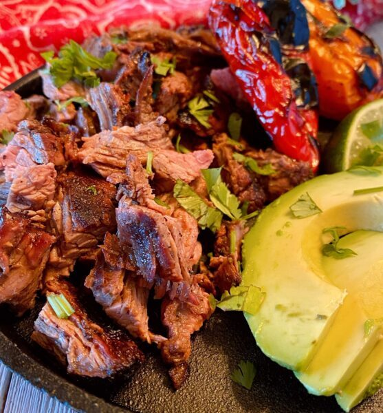 Chopped Carne Asada on a plate with roasted peppers and avocado.