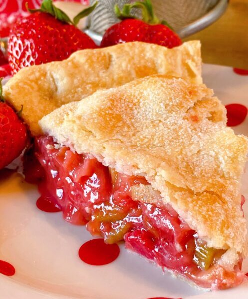 Slice of Strawberry Rhubarb Pie on a polka-dot plate upclose