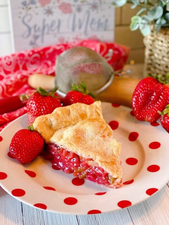 Big slice of Strawberry Rhubarb Pie on a fun polka dot plate with fresh strawberries surrounding it and a pretty background.