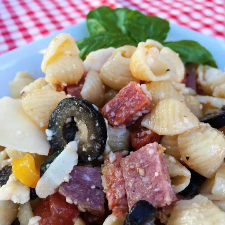 Bowl full of Antipasto pasta salad with fresh basil sprig