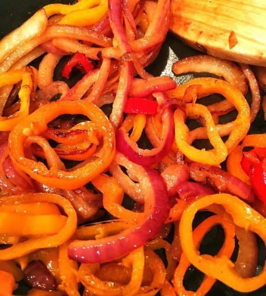 Caramelized onions and peppers in skillet.