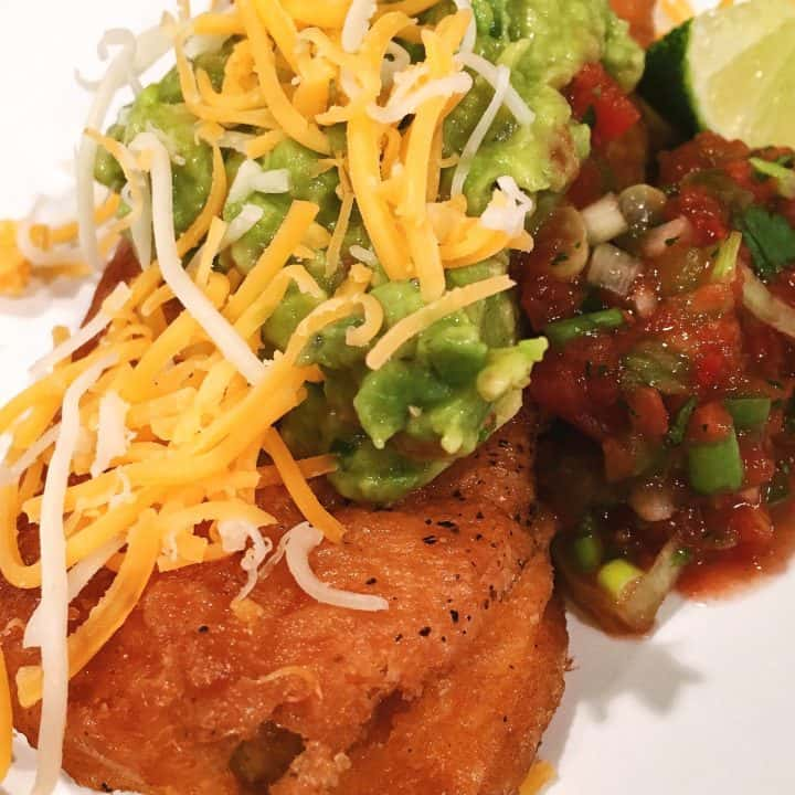 Homemade chili relleno topped with homemade salsa, guacamole, and cheese