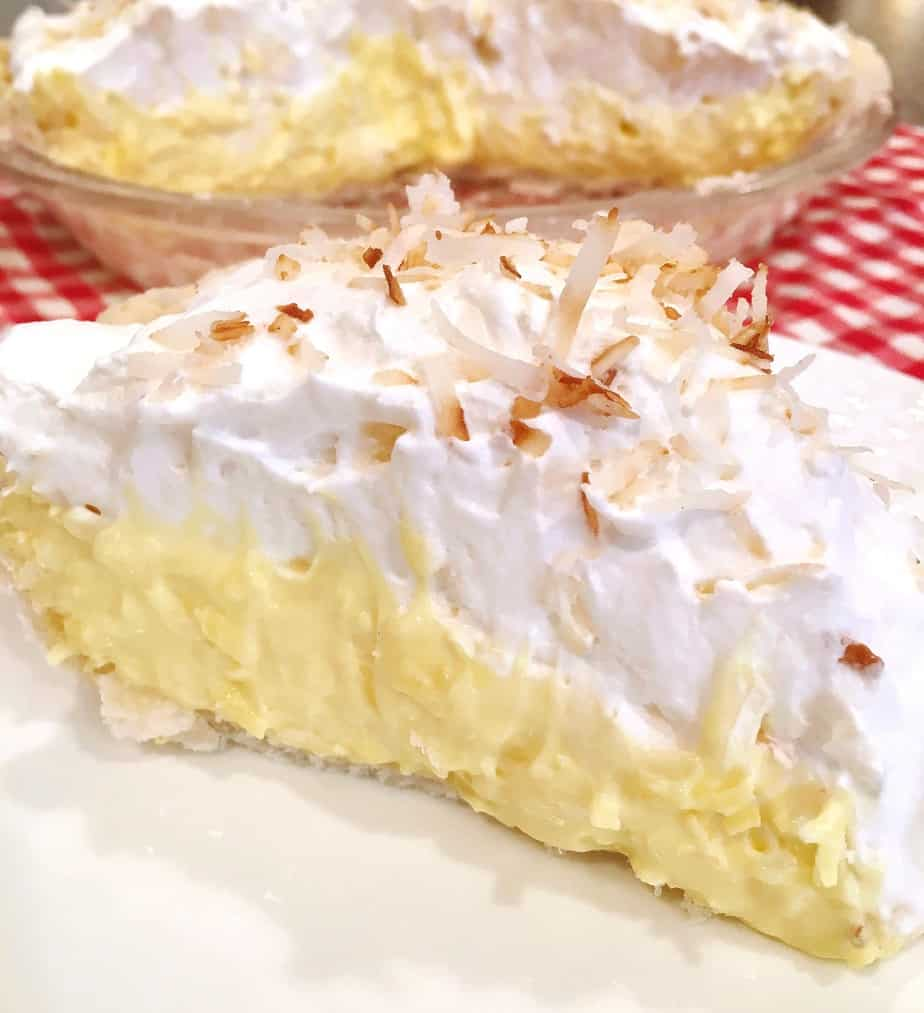 A large slice of easy Coconut Cream Pie on a white plate ready to eat!