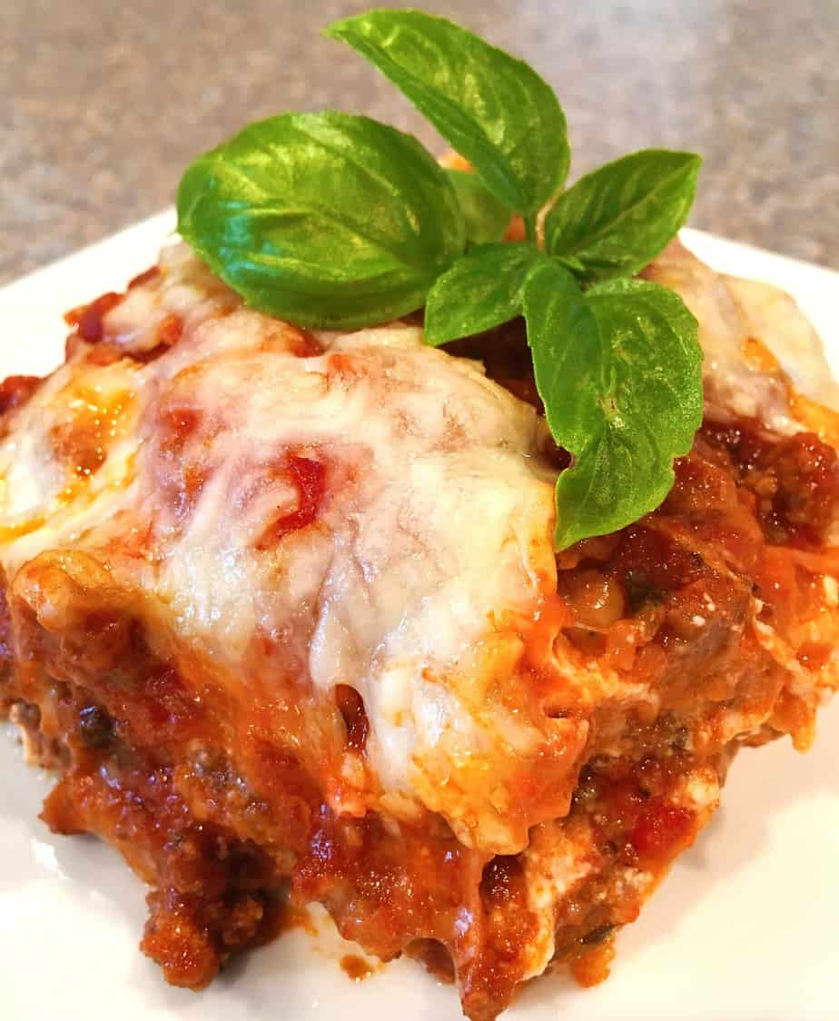 Serving of Eggplant Parmesan on a plate with fresh basil