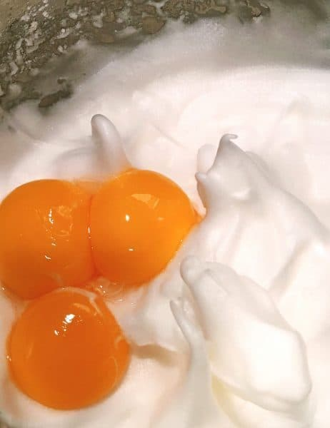 Egg whites beaten to stiff peaks with three egg yolks waiting to be folded into egg whites.