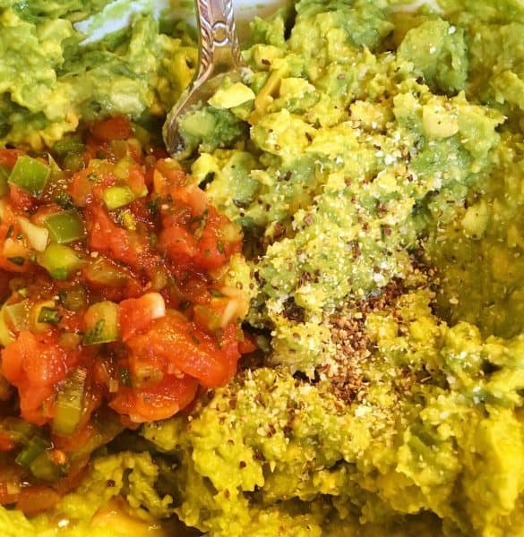 Mashed Haas Avocados with pepper, garlic salt, and a scoop of fresh salsa being mixed together. These ingredients create the best homemade guacamole.