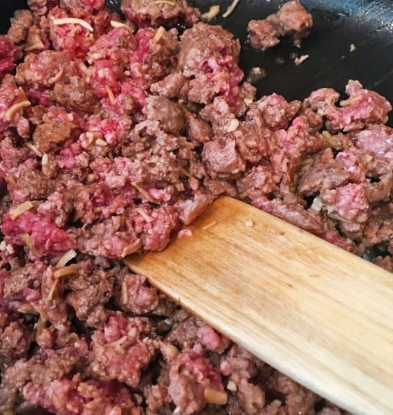 Hamburger meat with dried onion flakes in a skillet being browned over high heat.