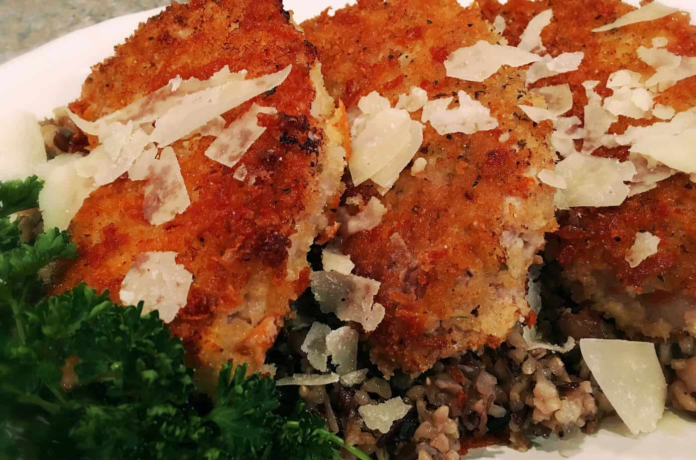 Paremsan Crusted Pork Chops on a bed of Wild Rice and sprinkled with Parmesan Cheese Flakes.