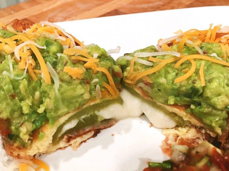 Perfectly Cut Chili Relleno's with cheese melted topped with fresh guacamole and grated cheese.