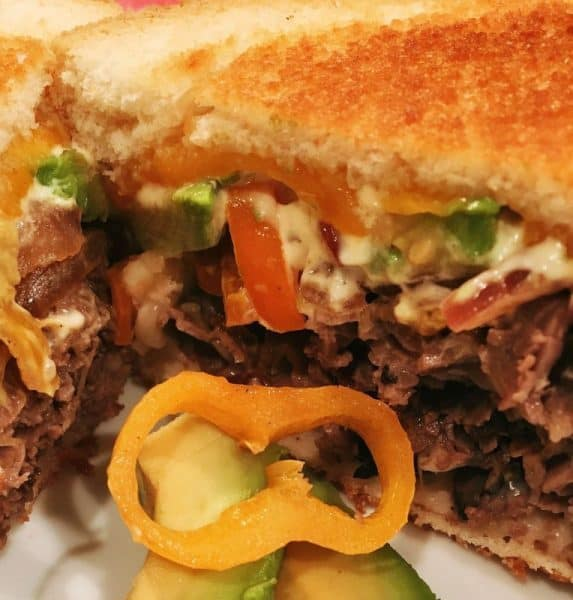 Two slices of toasted bread with roast beef, cheese, peppers and tomatos in between