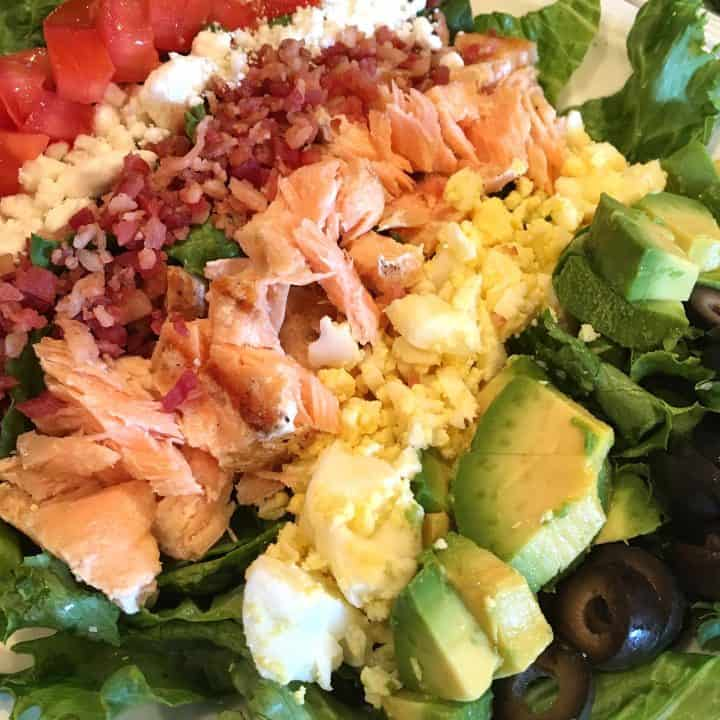 Plate filled with rows of delicious cobb salad toppings including delicious salmon