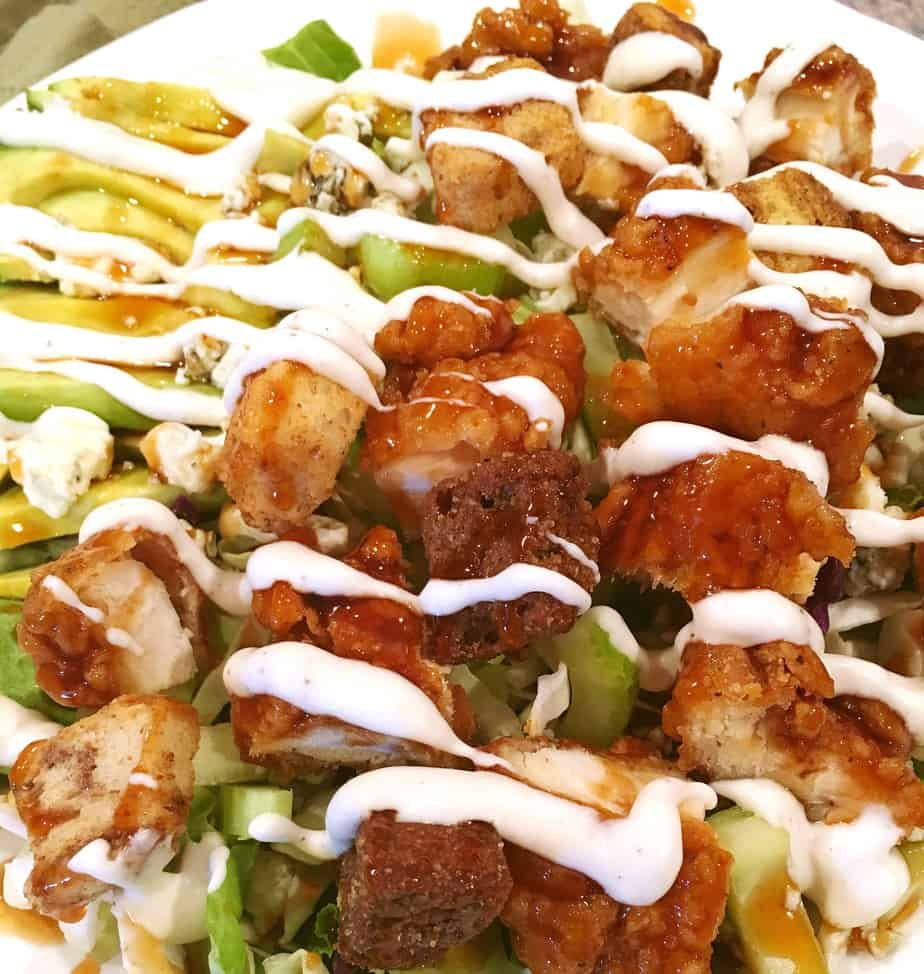 A green salad with cut up boneless buffalo wings