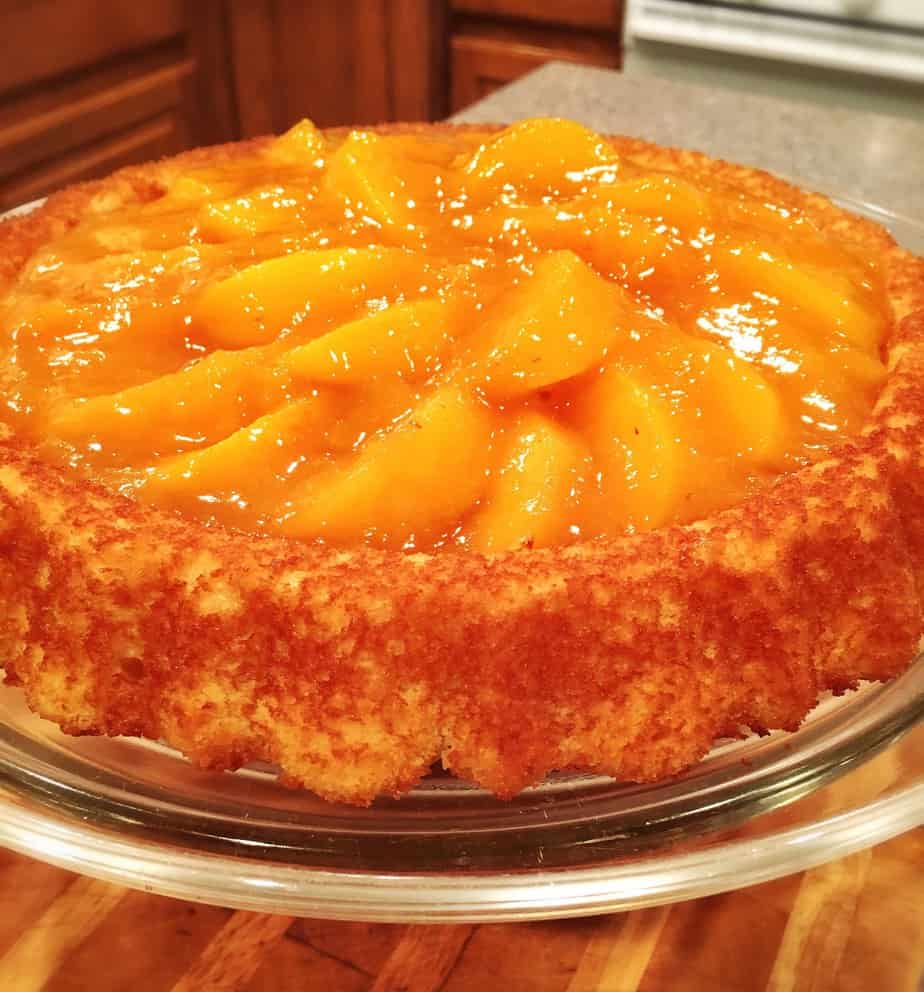 A cake with fresh peach slices and a golden glaze