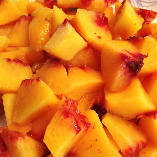 fresh cut up peaches ready for freezing for smoothies