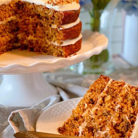 World's best carrot cake on cake stand with a slice on a plate in front