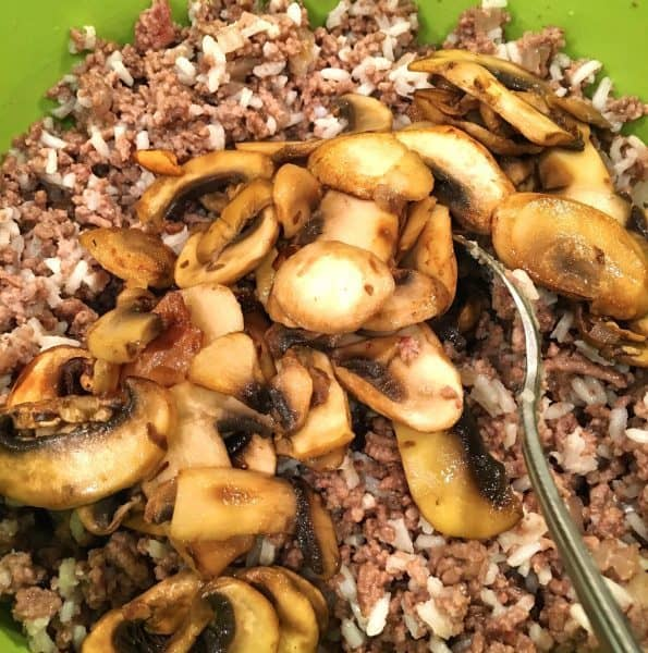 adding rice and mushrooms to stuffing mix for dinner in a pumpkin