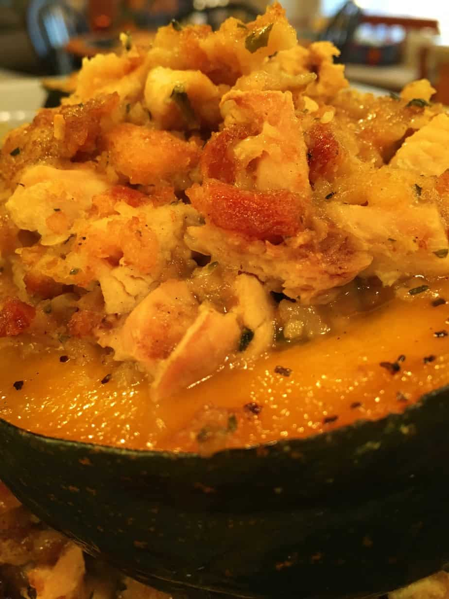 Acorn squash cut in half baked and filled with chicken and stuffing