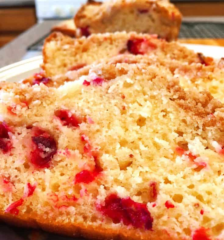 A light moist cranberry orange bread with cake like texture is topped with an amazing streusel topping and then drizzled with an orange zest glaze! It's simply the BEST! Perfect for breakfast during the Holidays!