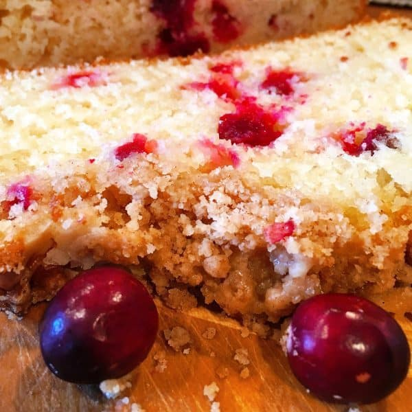 Slices of Cranberry Orange Bread with crumb topping and orange drizzle.