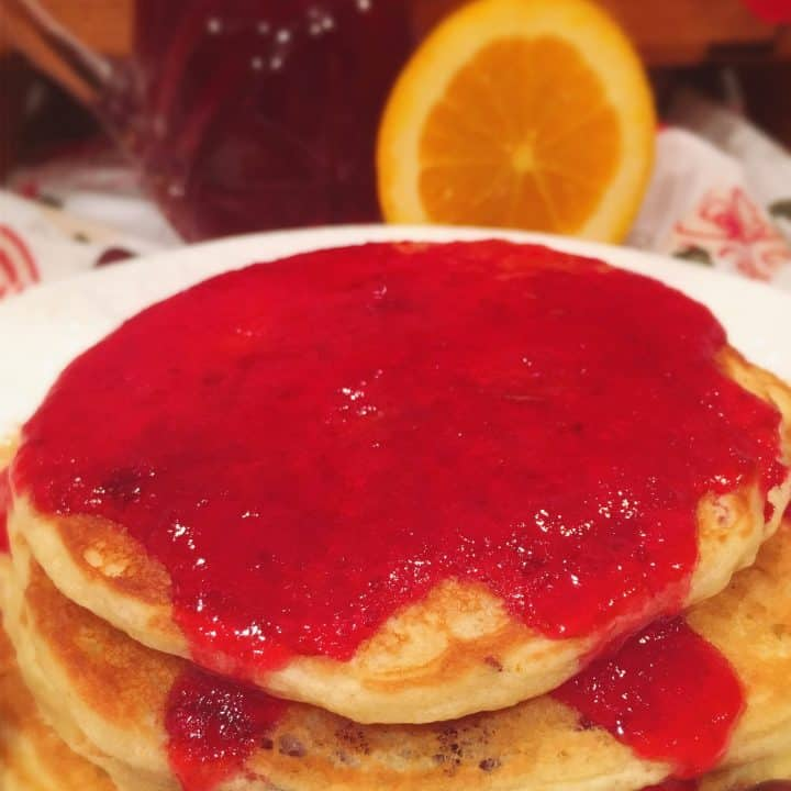Cranberry Orange Pancakes in a stack with syrup