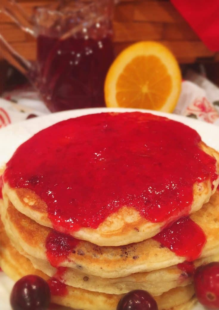Light and fluffy buttermilk pancakes are flavored with fresh chopped cranberries and orange zest and topped with an amazing fresh cranberry orange rum syrup! The perfect Christmas breakfast!