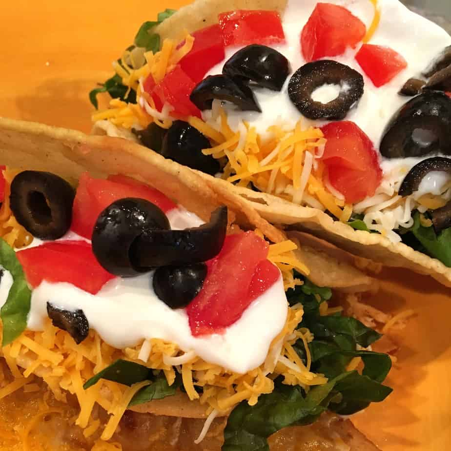 chicken shredded and cooked in a crook pot. Seasoned with mexican spices. Served in taco shells with tomato, olives, cheese and lettuce