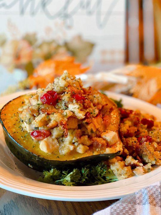 Stuffed Acorn Squash on a plate and festive Fall table setting.