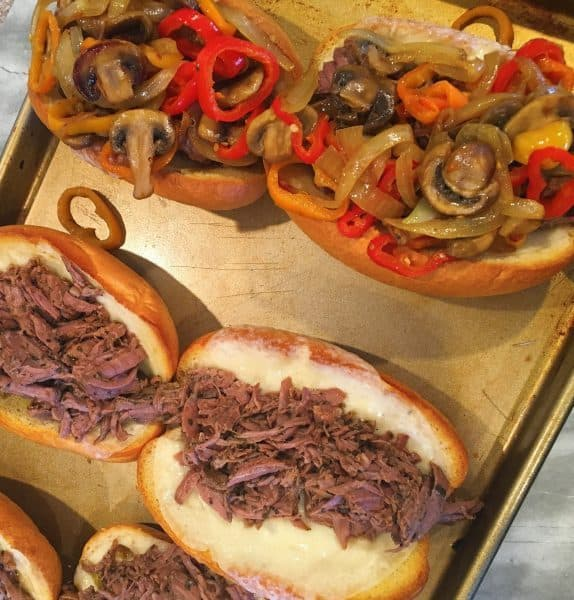 Italian Sub sandwiches being made with shredded beef with sauteed peppers and onions
