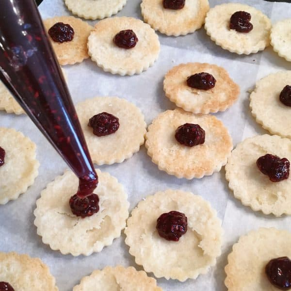 Linzer Cookie with Raspberry filling being pipped into center