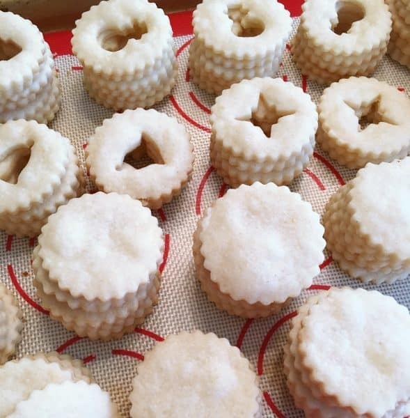 Linzer cookies baked on baking sheet ready for filling