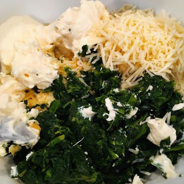 Spinach, garlic, chopped artichokes, Parmesan cheese and cream cheese in a large bowl ready to mix.