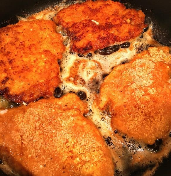 Fried chicken breast in the skillet.