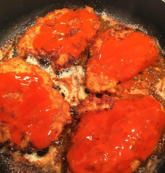 Fried chicken breast with Buffalo sauce drizzled over them