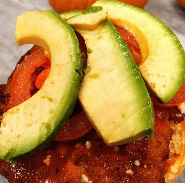 sliced avocado and tomato on top of chicken