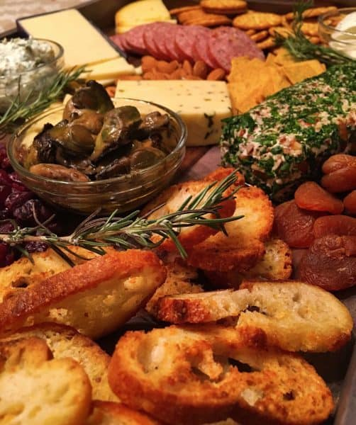 A delicious Cheese Board loaded with crackers, meats, cheeses, and dried fruits
