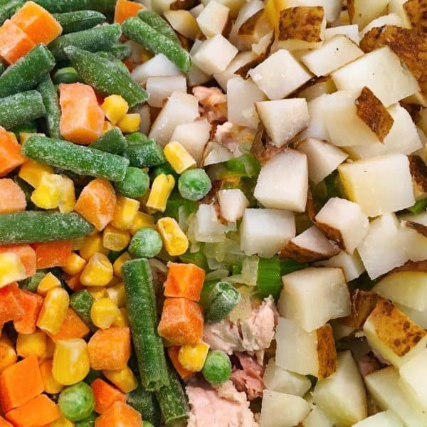 Adding frozen vegetables to potatoes and chicken