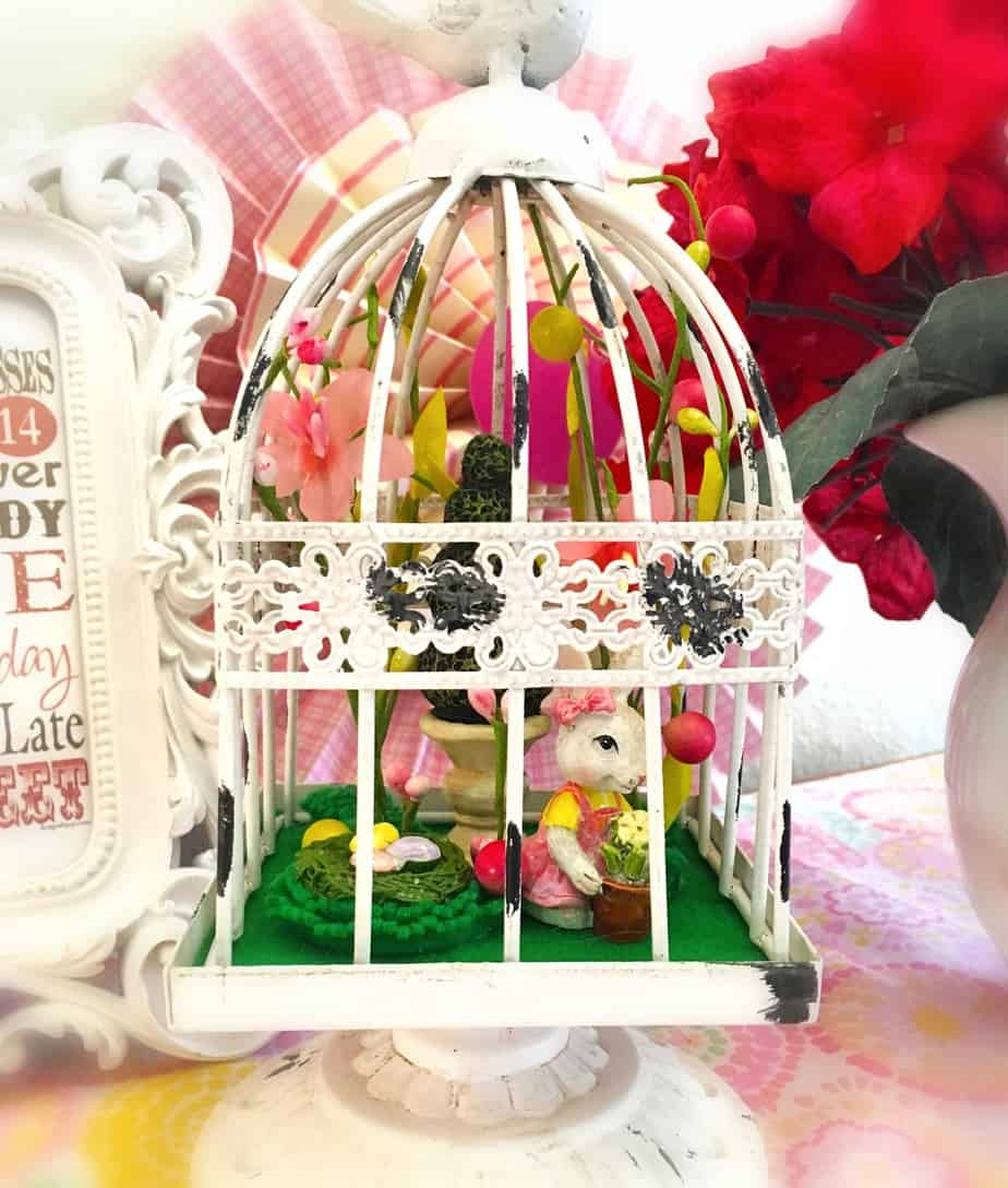 A white bird cage with various Easter decorations inside