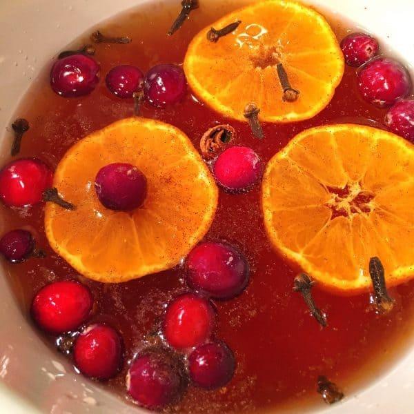 Slow Cooker full of cider, cranberries, cloves, and orange slices