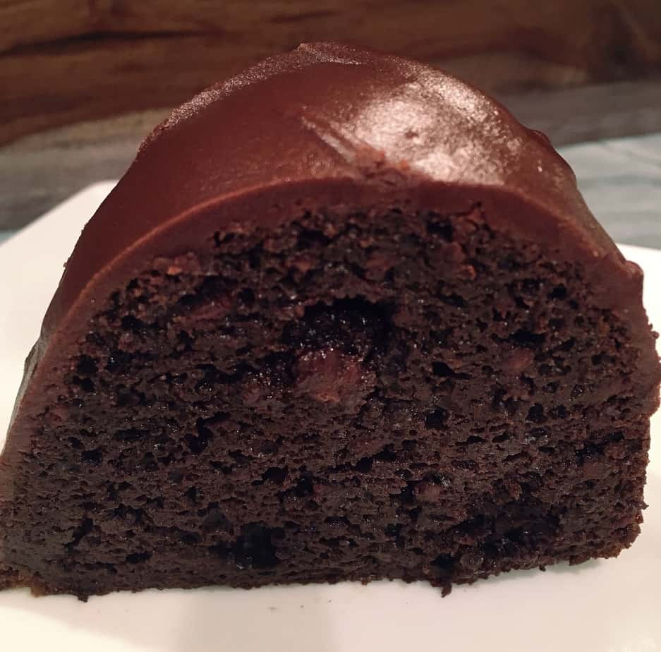 A delicious piece of chocolate cake with a chocolate frosting on top