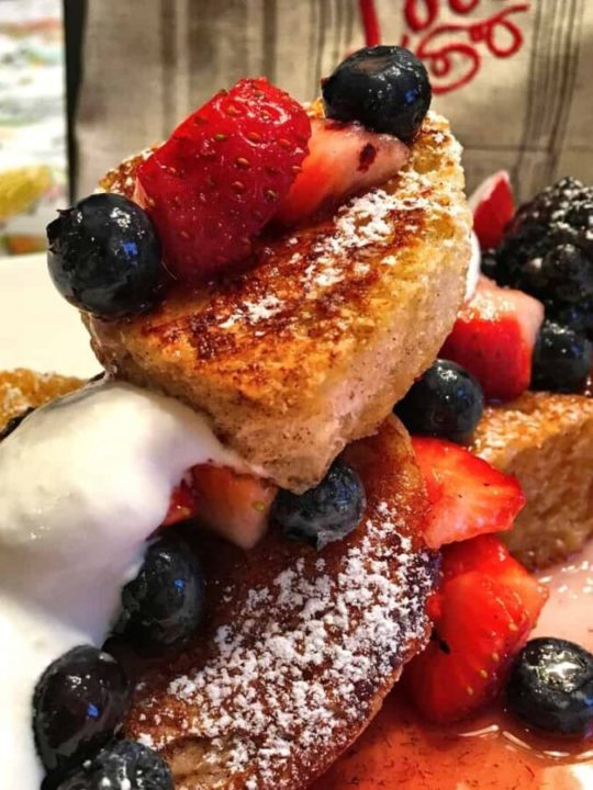 Heart shaped french toast with strawberries, blueberries and cream drizzled all over