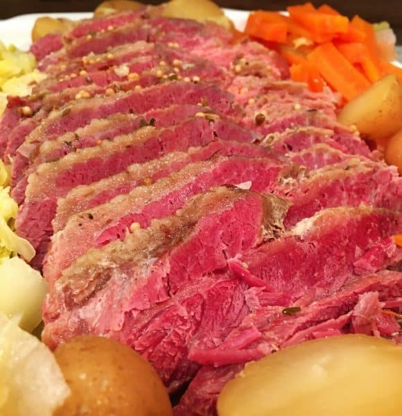 Sliced Corn Beef with potatoes, carrots, and cabbage.