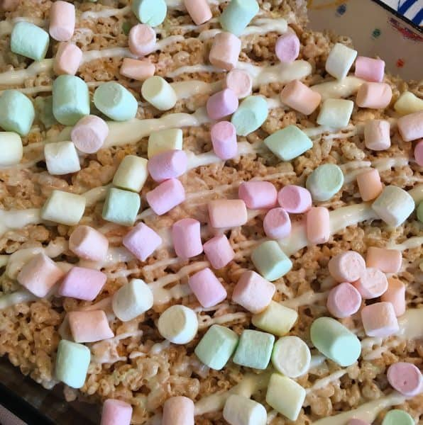 Rice Krispie treats drizzled with white chocolate and small pastel marshmallows
