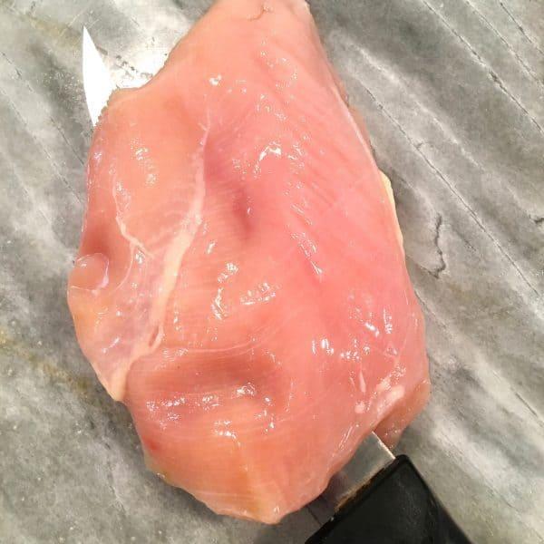 Chicken breast being fillet.