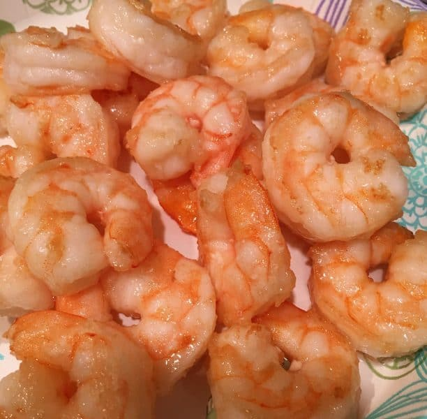 Cooked shrimp draining on a paper plate