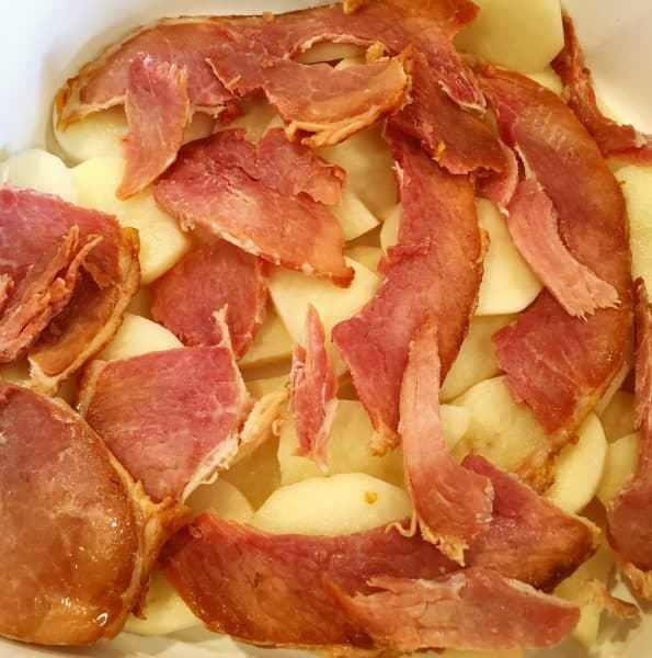 Layering sliced potatoes, ham, and white sauce in casserole dish