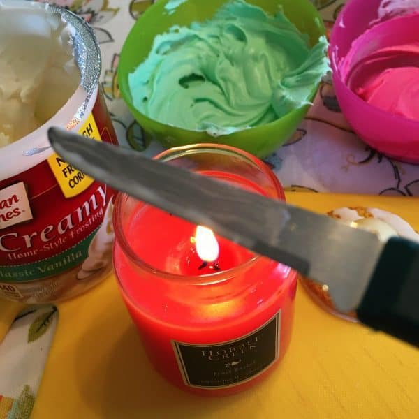 Heating up a knife over a candle and colored frostings