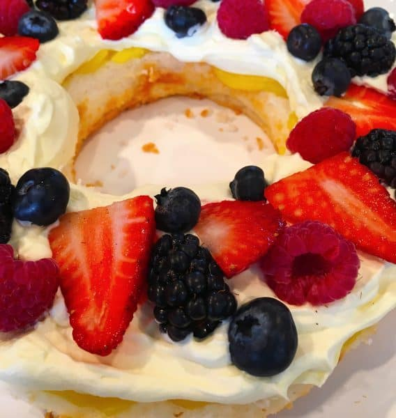 Placing fresh berries on top of lemon whipped cream frosting