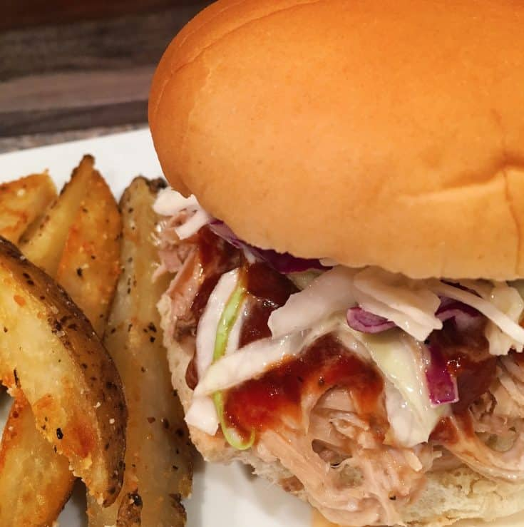 Easy and delicious smoke flavored pulled pork is piled high on top of a sandwich bun with BBQ sauce and sweet classic cole slaw. It's an AMAZING sandwich!