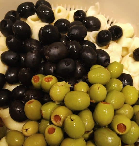 Olives, both green and black, with tortellini in strainer